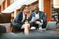 Business people reading a contract carefully two young with papers meeting in hotel lobby african businessman and caucasian women Stock Images