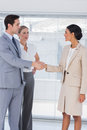 Business people shaking hands in bright office while colleague watching them Stock Images