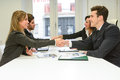 Business people shaking hands four finishing up a meeting Royalty Free Stock Image