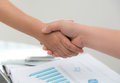 Business people shaking hands over business document Stock Photos