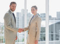 Business people shaking hands and smiling at camera in a bright office Stock Photos