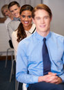 Business people sitting in a row happy smiling team Stock Photography