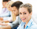 Business people sitting in a row smiling Stock Photo