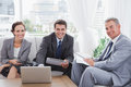 Business people smiling at camera while having a meeting in cosy room Stock Images