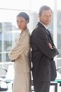 Business people standing back to back in office Royalty Free Stock Images