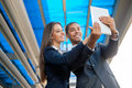 Business people taking selfie and looking at digital tablet young team outdoors a Stock Image