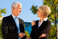Business people talking outdoors mature or senior standing in a park Stock Photos