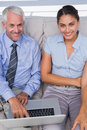 Business people using laptop on the couch and smiling up at came camera in staffroom Royalty Free Stock Image