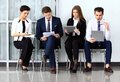 Business people waiting for job interview four candidates competing one position Royalty Free Stock Images