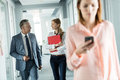 Business people walking in corridor with female colleague using mobile phone in foreground at office Royalty Free Stock Photo