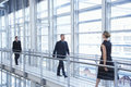 Business people walking by railing in modern office full length of Royalty Free Stock Photography