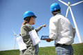 Business people working in turbine field engineers looking at wind site with tablet Royalty Free Stock Images
