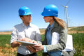 Business people working in turbine field engineers using tablet on wind site Stock Images