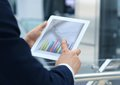 Business person analyzing financial statistics displayed on the tablet screen Royalty Free Stock Photos