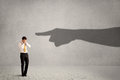 Business person looking at huge shadow hand pointing at him conc concept on background Royalty Free Stock Photo