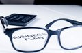 Business plan words see through glasses lens near calculator, business concept Royalty Free Stock Photo