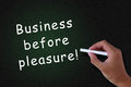 Business before pleasure close up of hand writing on a blackboard strive struggle commercial concept Royalty Free Stock Images