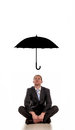 Business protection a man sitting on the floor with a umbrella over hip as a concept Stock Images
