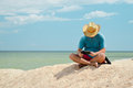 Business resting man sitting at seaside with tablet computer in hat on sandy beach and on summer sea outdoors background Royalty Free Stock Photography