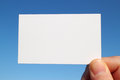 Business sized white card close up in the blue sky Royalty Free Stock Photo
