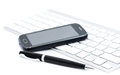 Business smartphone on the keyboard with pen isolated white Stock Photo