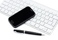 Business smartphone on the keyboard with pen isolated white Royalty Free Stock Photography