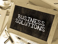 Business Solutions Handwritten by white Chalk on a