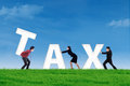 Business team builds a tax word group of or complete on the green field Stock Images