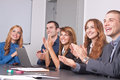 Business team five young people applauding focus is on the girl on the right side Royalty Free Stock Photos