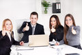 Business team four happy people showing thumbs up in the office looking at camera Stock Image
