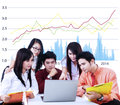 Business team having a discussion using laptop on growth graph background Stock Photo