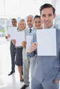 Business team in a line holding white pages smiling at camera Stock Images