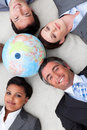 Business team lying on the floor around a globe Royalty Free Stock Images