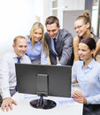 Business team with monitor having discussion technology and office concept smiling computer in office Stock Photos