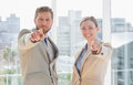 Business team pointing at camera and smiling in office Stock Photography