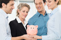 Business team saving money group of businesspeople together holding piggy bank Royalty Free Stock Image