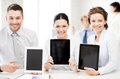 Business team showing tablet pcs in office smiling Stock Photography