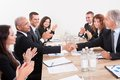 Business Team Sitting At Table And Applauding Royalty Free Stock Images