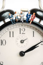 Business team sitting on top of the giant clock macro photo Royalty Free Stock Photography