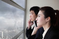 Business team speaking phone and looking through window with city background with serious face asia hong kong asian Stock Photo