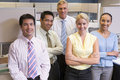 Business team standing in cubicle smiling Stock Photos