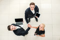 Business team top view of three business people in formal wear standing and discussing and shake hands and folding their hands on Stock Photos