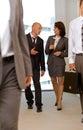 Business team walking thru corridor and talking Royalty Free Stock Image