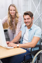 Business team working together at desk smiling at camera Royalty Free Stock Photo