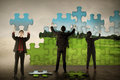 Business teamwork assembling puzzle pieces create green environt Royalty Free Stock Photo
