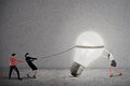 Business teamwork pulling bright light bulb grey background Stock Images