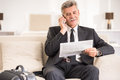 Business trip senior man talking by phone and holding newspaper while sitting at the sofa in hotel room Stock Images