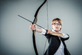 Business woman aiming with bow and arrow grey background Royalty Free Stock Image