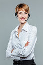 Business woman with arms crossed and headset on smiling to the camera isolated grey Royalty Free Stock Photos