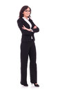 Business woman with arms folded full length picture of a young standing her hands and looking at the camera a smile on her face on Royalty Free Stock Photos